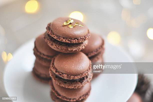Stack of chocolate macaroons on white plate