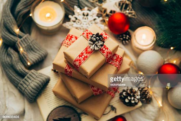 stack of christmas gifts, decorations and knitted sweater - christmas gifts stock photos and pictures