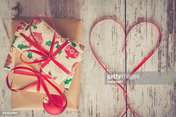 Stack of Christmas presents, red Christmas bauble and ribbon shaped like a heart on wood