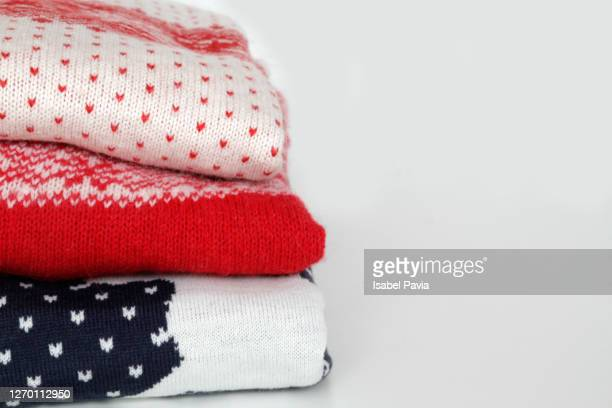 stack of christmas sweaters - warm clothing stock pictures, royalty-free photos & images