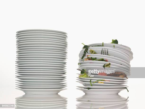 Stack of Clean Dishes Beside a Stack of Dirty Dishes