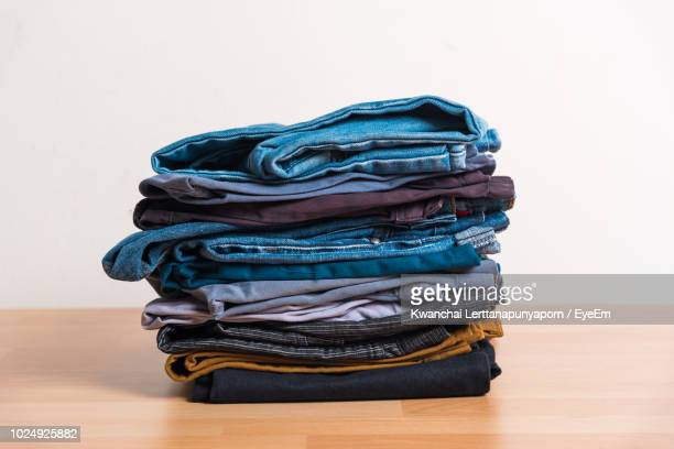 stack of clothing on table against wall - clothing stock pictures, royalty-free photos & images