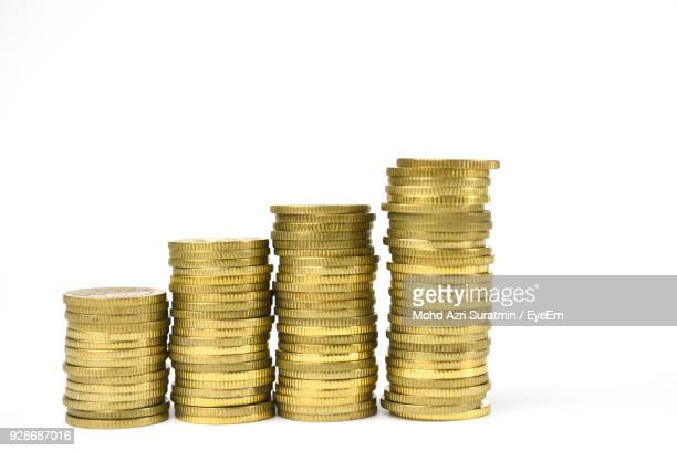 stack of coins against white background - coin stock pictures, royalty-free photos & images