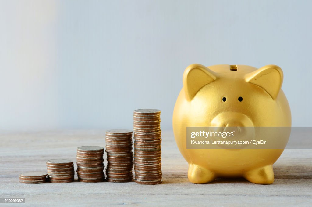Stack Of Coins By Piggy Bank On Table Against Wall : Foto de stock
