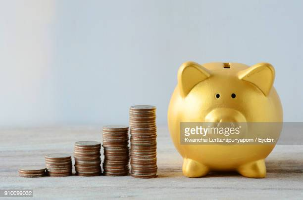 Stack Of Coins By Piggy Bank On Table Against Wall