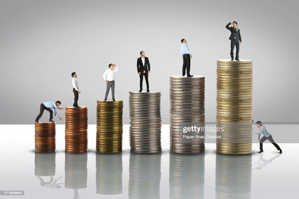 Stack of coins from low to high,tiny men on top : Stock Photo