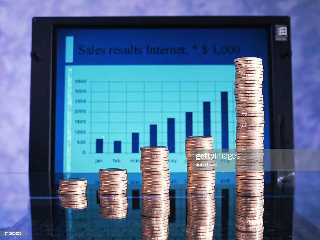 Stack of coins in front of laptop displaying bar graph : Stock Photo
