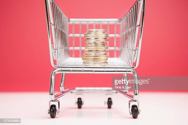 Piles de pièces de monnaie au panier d'achats