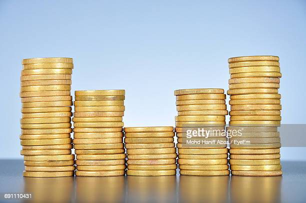 Stack Of Coins On Table Against Colored Background