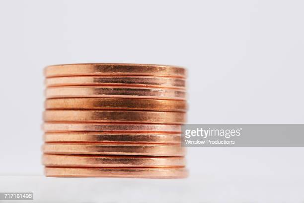 stack of coins on white background - us penny stock pictures, royalty-free photos & images