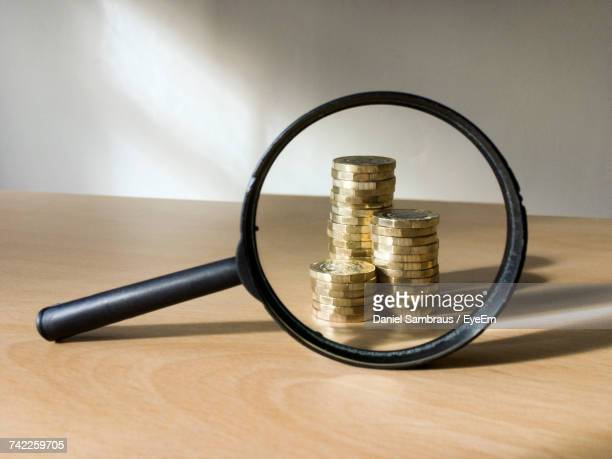 Stack Of Coins Seen From Magnifying Glass On Table