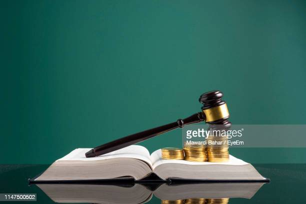 stack of coins with gavel over open book on table against green background - law stock pictures, royalty-free photos & images