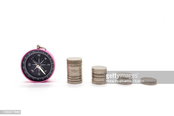stack of coins with navigational compass on white background - compass stock pictures, royalty-free photos & images