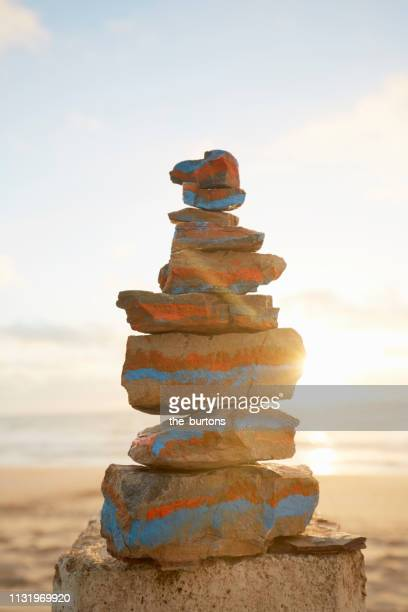 Stack of colorful balanced stones at the beach during sunset
