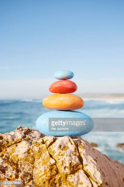 stack of colorful balanced stones at the sea - stone object stock pictures, royalty-free photos & images