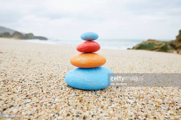 stack of colorful balanced stones on the beach - stack rock stock pictures, royalty-free photos & images
