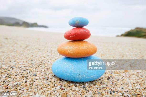 stack of colorful balanced stones on the beach - 石塚 ストックフォトと画像