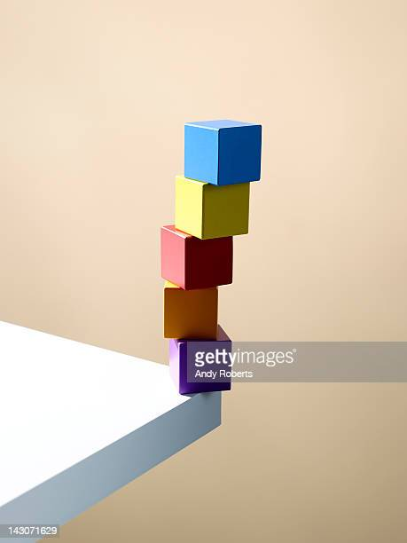stack of colorful cubes on table corner - vulnerability stock pictures, royalty-free photos & images