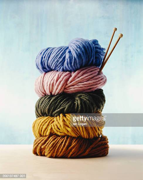 stack of colorful yarns with knitting needles - wool stock pictures, royalty-free photos & images