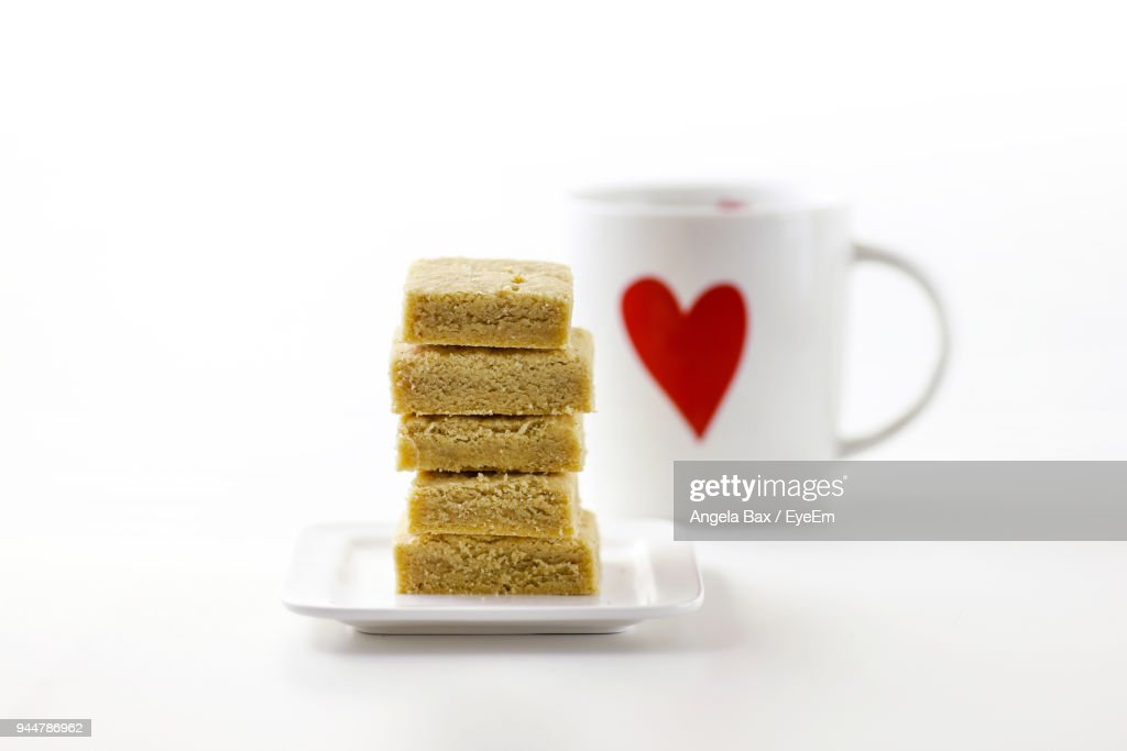 Stack Of Cookies In Plate Against Mug Over White Background : Stock Photo
