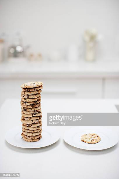 stack of cookies on plate next to single cookie on plate - imbalance stock pictures, royalty-free photos & images