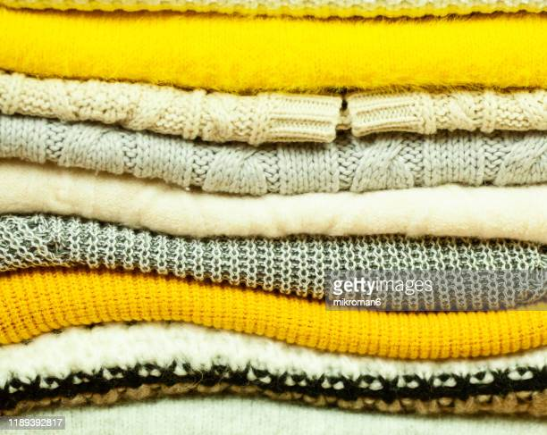 a stack of cozy winter cable knit sweaters in different colors - herbst winter kollektion stock-fotos und bilder