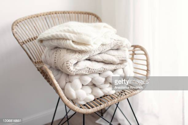 stack of cozy wool white knitted sweaters on wicker armchair. pile of merino and cashmere winter clothes. hygge style. warm concept. - cashmere stock pictures, royalty-free photos & images