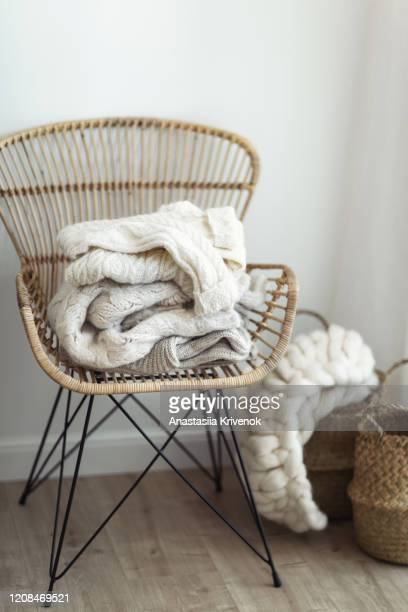 stack of cozy wool white knitted sweaters on wicker armchair. pile of merino and cashmere winter clothes. hygge style. warm concept. - hygge stock-fotos und bilder