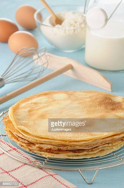 Stack of crepes with ingredients and utensils