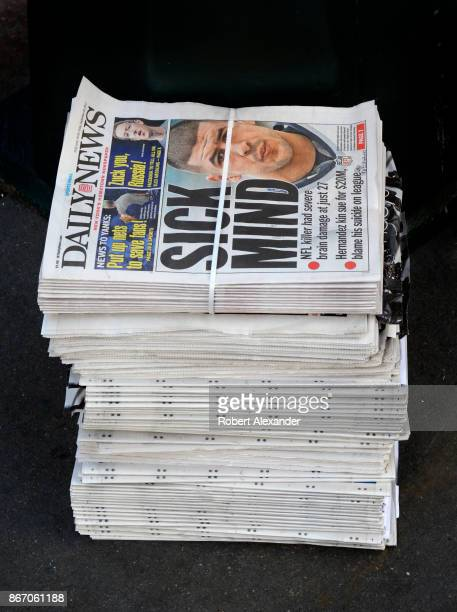 A stack of Daily News tabloid newspapers sit on a sidewalk in New York New York The headline refers to the results of a autopsy on former NFL...