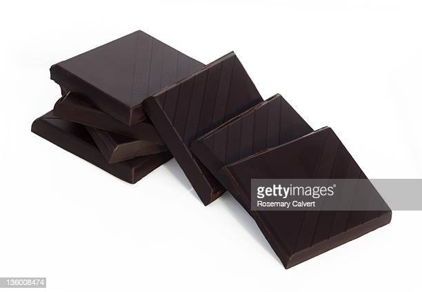 Stack of dark rich chocolate partly toppled.