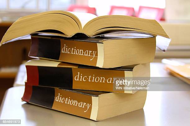 stack of dictionaries on a desk - dictionary stock pictures, royalty-free photos & images