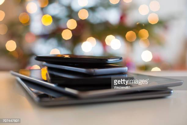 Stack of digital tablets and smartphones at Christmas time, close-up