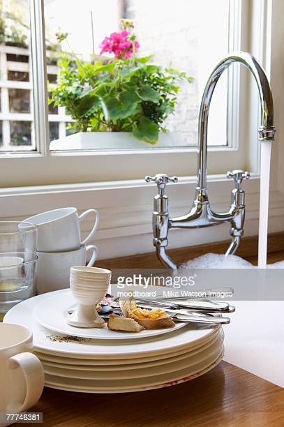 Stack of Dirty Dishes Next to Sink