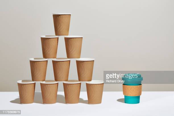 A stack of disposable coffee cups next to a reusable coffee cup