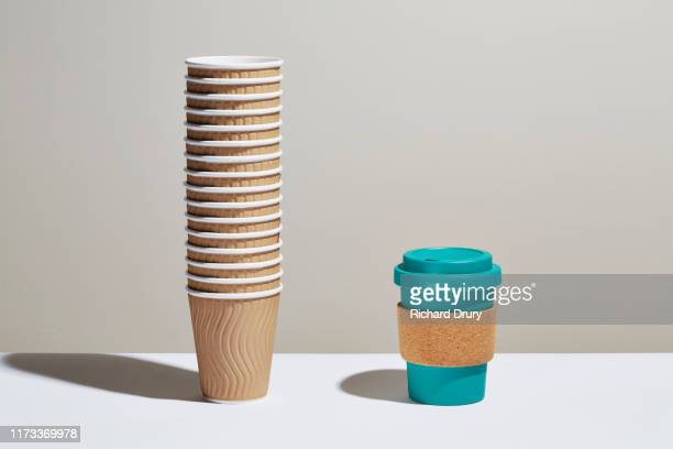 a stack of disposable coffee cups next to a reusable coffee cup - cup stock pictures, royalty-free photos & images