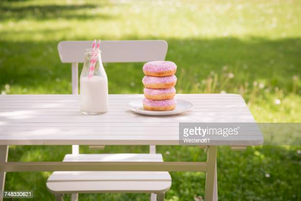 Stack of donuts and milk bottle on garden table