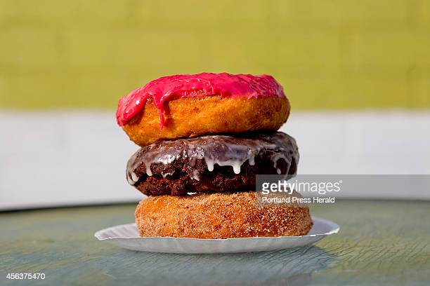 A stack of donuts from top include a raspberry glazed dark chocolate sea salt and vegan cinnamon sugar at The Holy Donut on Park Avenue in Portland...