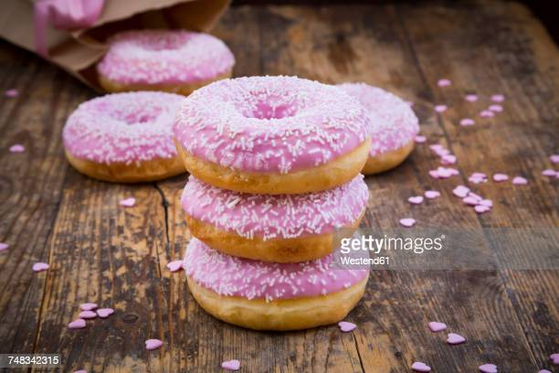 stack of doughnuts with pink icing and sugar granules on wood - donuts - fotografias e filmes do acervo