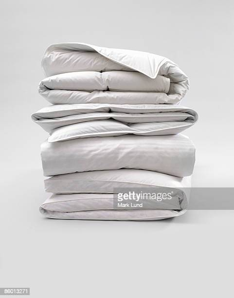 stack of down comforters - bedclothes stock pictures, royalty-free photos & images