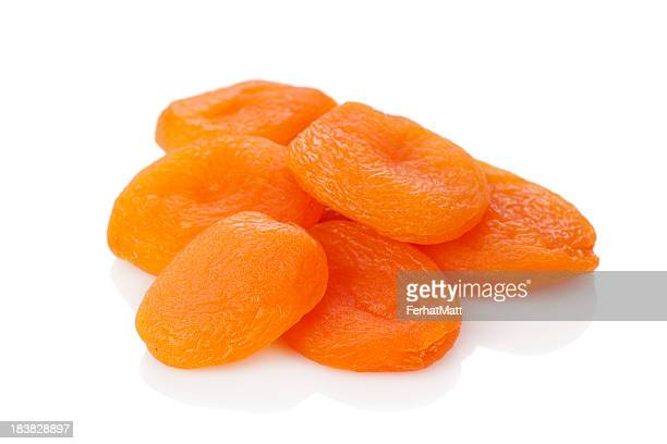 A stack of dried apricots against a white background
