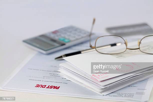 Stack of envelopes with pen, calculator, glasses and credit card