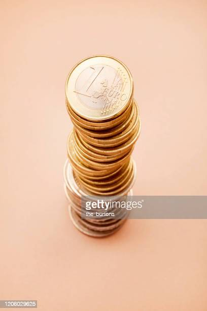 stack of euro coins on brown background - group e stockfoto's en -beelden