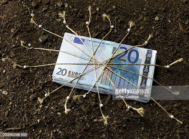 stack of euros tied down on soil with string and straight pins - twenty euro banknote stock photos and pictures