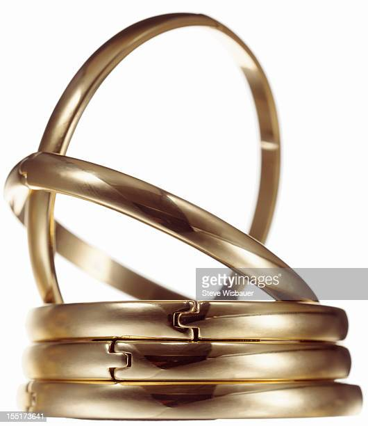 A stack of five clasping gold bangle bracelets