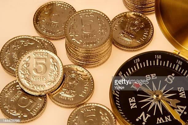 Stack of five rupees coins beside a compass