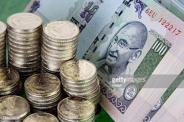 Stack of five rupees coins beside paper currency