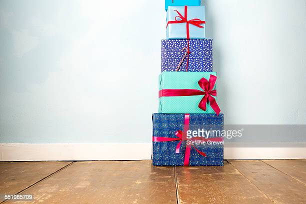 Stack of five wrapped christmas gifts on wooden floor