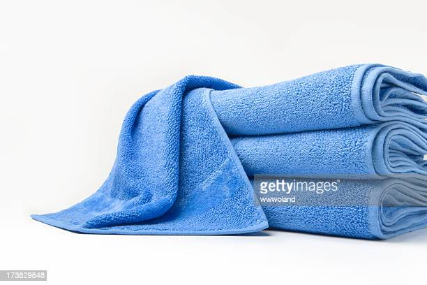 stack of folded blue cotton towels with one draped on top - towel stock pictures, royalty-free photos & images