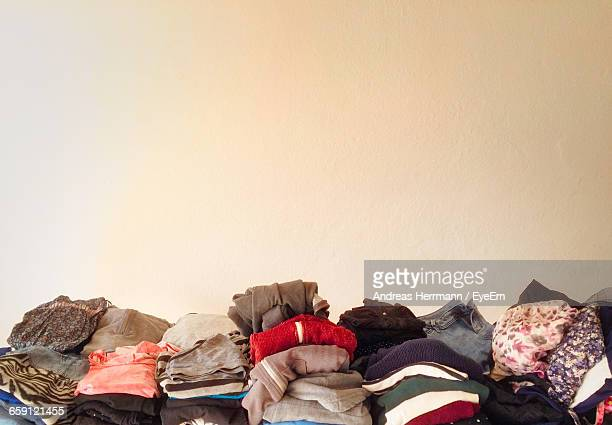 Stack Of Folded Clothes Against Wall